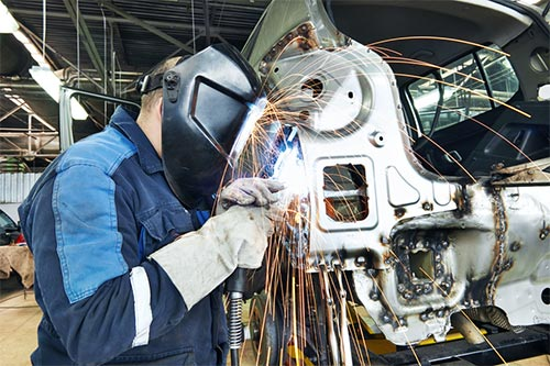 Welder working on vehicle